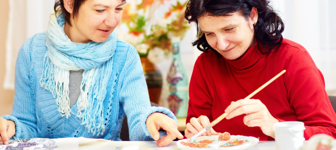 staff person helping participant with art project