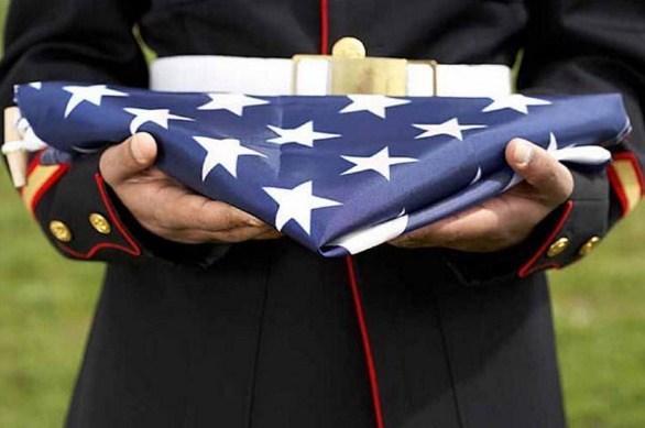 folded U.S. flag held by soldier in uniform